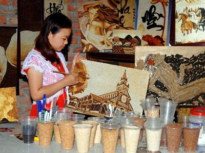 Đặng Thị Thúy Kiều đang hoàn thành bức tranh từ những hạt gạo.
